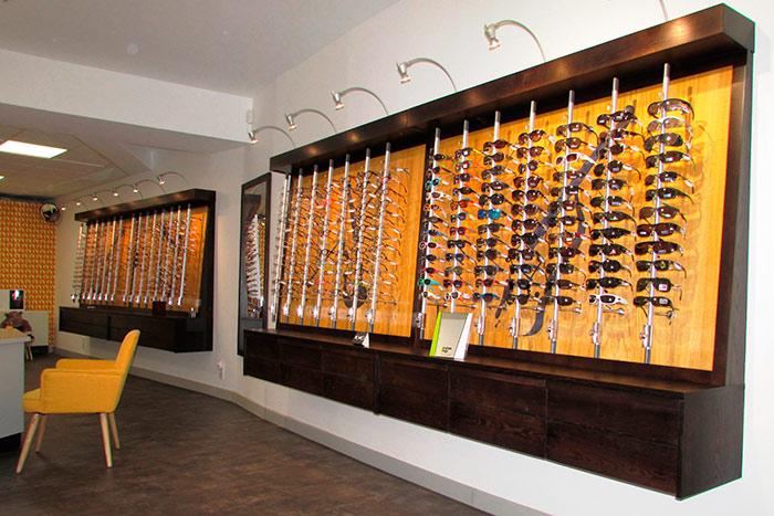 04-Opticien-magasin-presentoirs-a-lunettes-en-chene-teinte-noir-vernis-peintures-instruments-de-musique-a-cordes-sur-les-panneaux-de-fonds-et-vernis