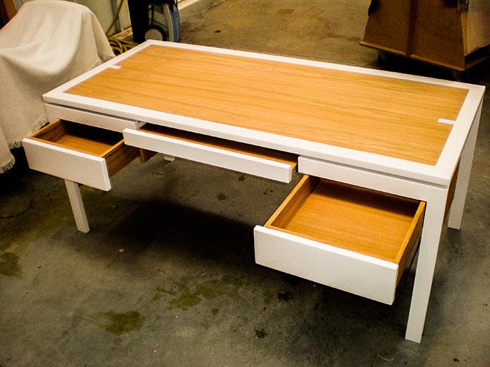 Bureau-plateau-et-tiroirs-en-chataigne-vernis-cadre-du-plateau-et-facades-tiroirs-en-cuir-blanc-mat-structure-pietement-en-metal-thermolaque-blanc-brillant-passe-cable-cuir-(1)